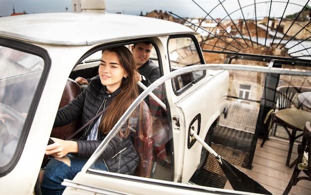 Paar auf dem dach eines hauses in einem alten auto.