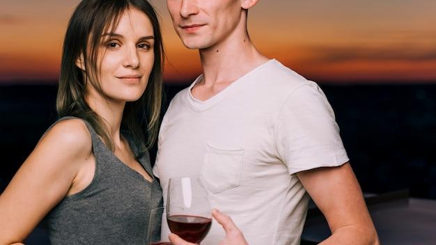 Paar auf dem dach im morgengrauen halbtotale