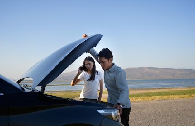 Paar auf der straße, das probleme mit einem auto hat. paar nach einer autopanne am straßenrand