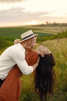 Paar auf einem feld. frau in einem braunen kleid.