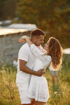 Paar auf einem feld. frau in einem weißen kleid. sonnenuntergang hintergrund.