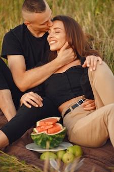 Paar auf einem feld. frau in einer schwarzen bluse. menschen mit wassermelone.