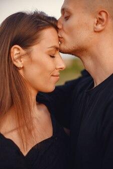 Paar auf einem feld. frau in einer schwarzen bluse.