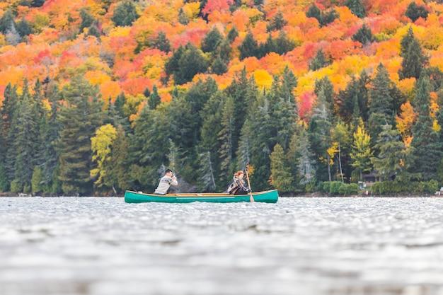 Paar auf einem kanu am see im herbst, kanada