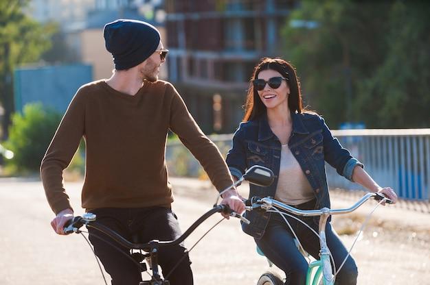 Paar auf fahrrädern. schönes junges paar, das fahrrad fährt und sich mit einem lächeln ansieht