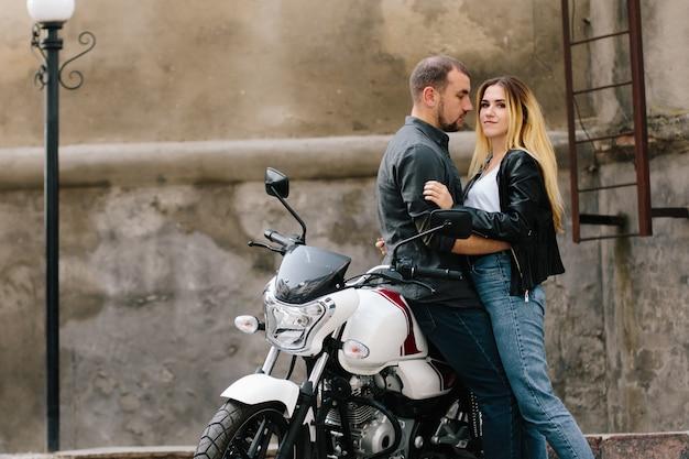 Paar auf motorrad in der nähe von altbau