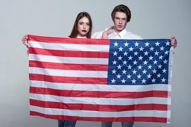 Paar auf ruhigen gesichtern hält die flagge der usa paar begrüßt den besuch der usa-typen und -mädchen, die stolz darauf sind, amerikaner mit grauem hintergrund sprachschulkonzept zu sein