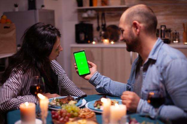 Paar aufpassendes telefon mit grünem bildschirm. glücklicher mann und frau, die auf der grünen bildschirmschablone chroma-schlüssel isolierte smartphone-anzeige mit technologieinternet betrachten, die am tisch in der küche sitzt.