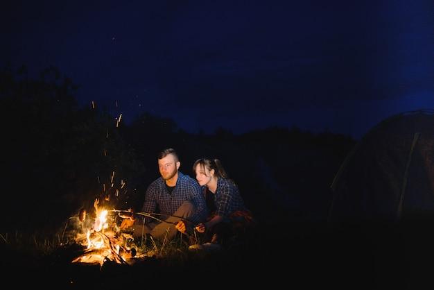Paar backen von würstchen am feuer und entspannen am lagerfeuer im wald in der nacht