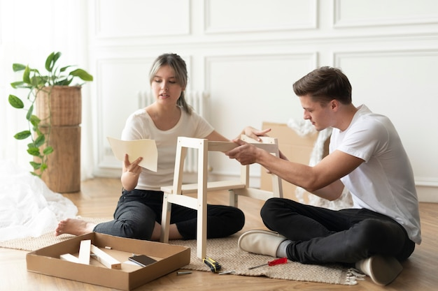 Paar baut einen diy-stuhl von grund auf zusammen
