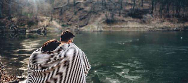 Paar bedeckt mit decke am see sitzen