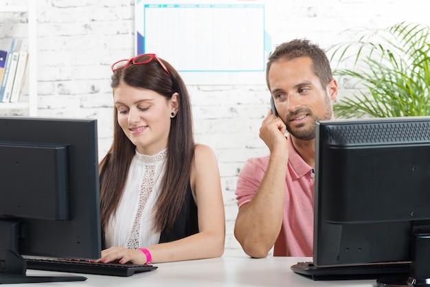 Paar bei der arbeit im büro, mann am telefon