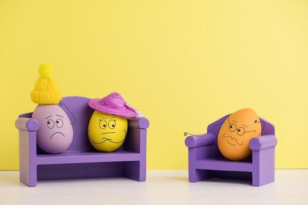 Paar bei einem psychologen. osterferienkonzept mit niedlichen eiern mit lustigen gesichtern. unterschiedliche emotionen und gefühle. psychische gesundheit in der familie