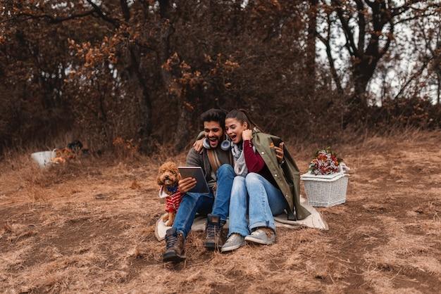 Paar beim picknick, das in der decke sitzt und tablette benutzt. neben ihnen hund und korb mit futter. herbstzeit.