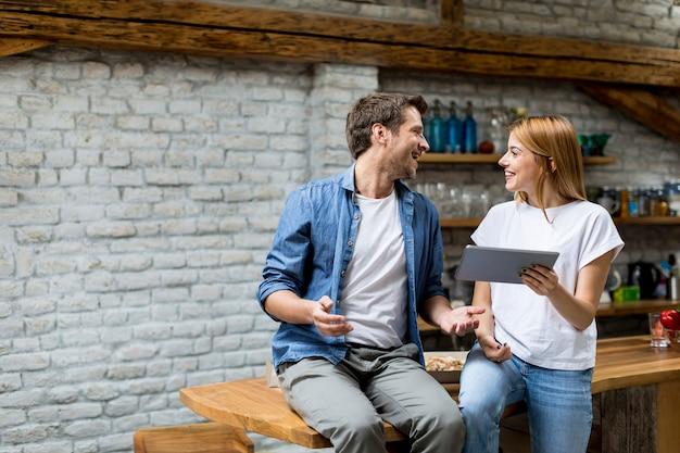 Paar benutzt eine digitale tablette und lächelt beim auf dem tisch sitzen zu hause