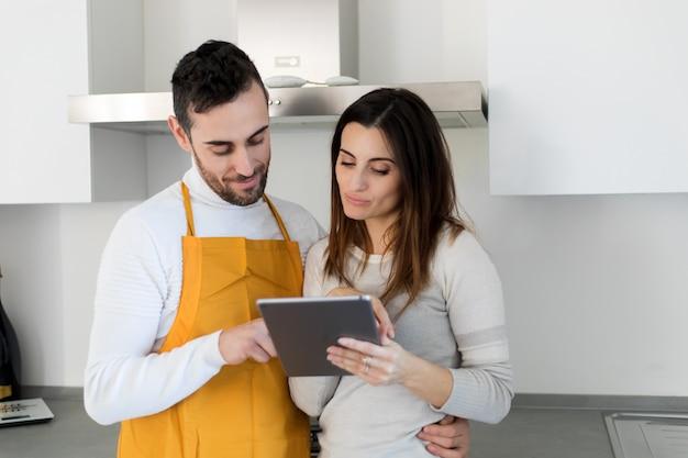 Paar bereit zu kochen, ein rezept mit einem digitalen tablett wählend