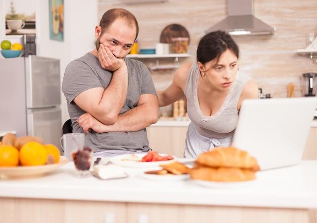 Paar besorgt über die schlechten nachrichten, die der ehemann morgens beim frühstück erhielt. unglücklicher, gestresster, frustrierter wütender negativer und verärgerter freiberufler im pyjama, der beim morgendlichen essen zu hause schreit