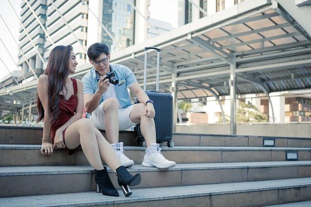 Paar betrachtet ihre fotos auf dem bildschirm ihrer kamera.