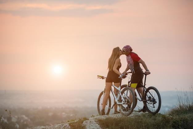 Paar biker küssen auf einem hügel