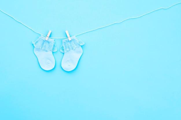 Paar blaue süße babysocken, die an der wäscheleine hängen