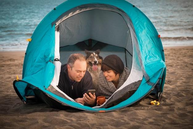 Paar blick auf das smartphone und spaß in einem zelt im freien camping am strand hund border collie hinter ihnen in die kamera schaut. helle farben und alternatives urlaubsfamilienkonzept. wo