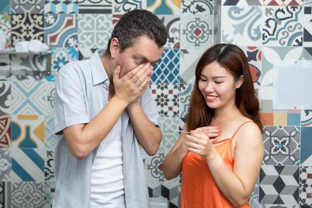 Paar blick auf schwangerschaftstest im badezimmer