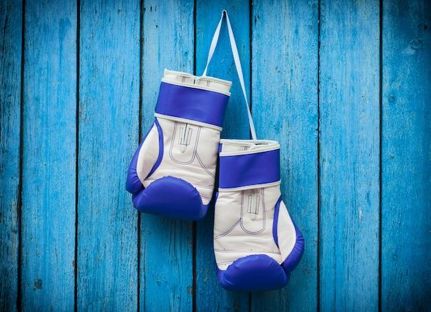 Paar boxhandschuhe, die an einem nagel hängen