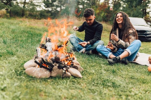 Paar braten marshmallows über dem lagerfeuer