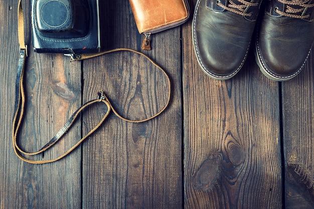 Paar braune lederschuhe und eine alte vintage-kamera