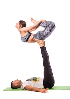 Paar, das akro-yoga im weißen studio praktiziert. acro yoga konzept. paar yoga. yoga flexibilitätskurs training
