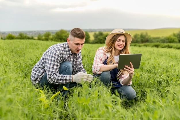 Paar, das am bauernhof mit tablette arbeitet