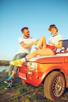 Paar, das am strand an einem sommertag nahe fluss ausruht. kaukasischer mann und frau, die bier trinken