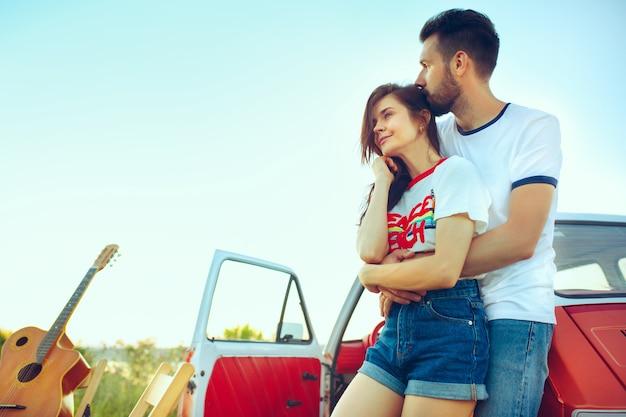 Paar, das am strand an einem sommertag nahe fluss ausruht. kaukasischer mann und frau