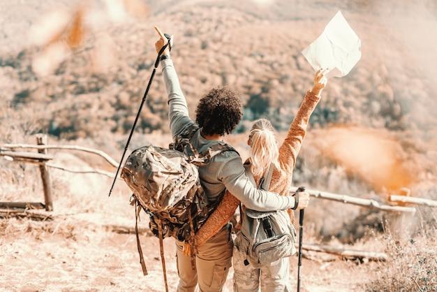 Paar, das an der punktansicht umarmt. frau hält karte, während mann stock hält. rücken gedreht. wandern in der natur am herbstkonzept.