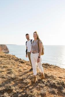 Paar, das an einer küste neben dem ozean geht