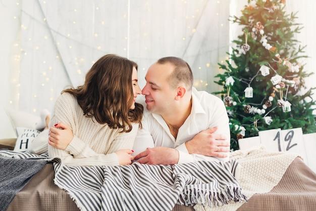 Paar, das auf dem bett nahe dem weihnachtsbaum liegt