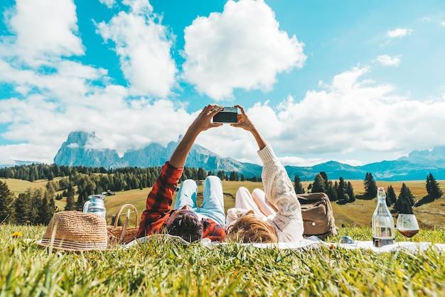 Paar, das auf dem gras liegend tirolalpen besucht. freund und freundin in der liebe, die ein foto der berglandschaft mit weinlesekamera - weinlesefilter - fernwehkonzept macht