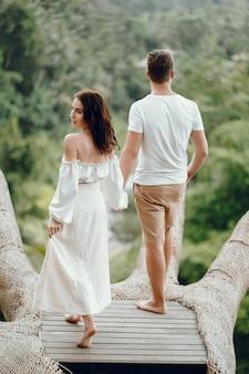 Paar, das auf einem waldhintergrund auf einem bali steht