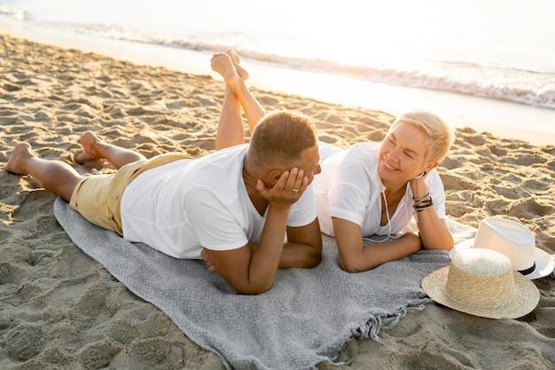 Paar, das auf handtuch am strand legt