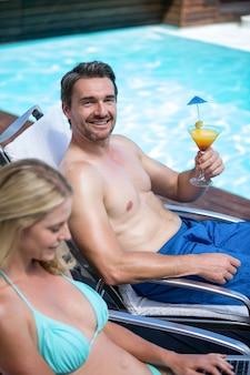 Paar, das auf sonnenliege nahe pool sitzt