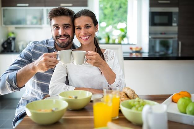 Paar, das beim frühstück eine tasse kaffee röstet
