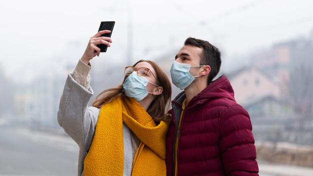 Paar, das bilder mit dem smartphone beim tragen der medizinischen maske macht