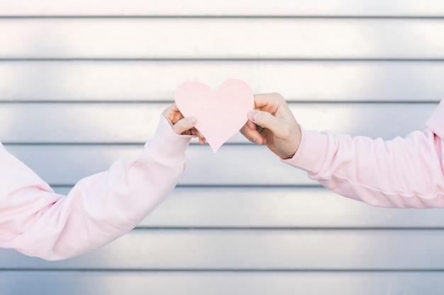 Paar, das dekoratives papiersymbol des herzens hält