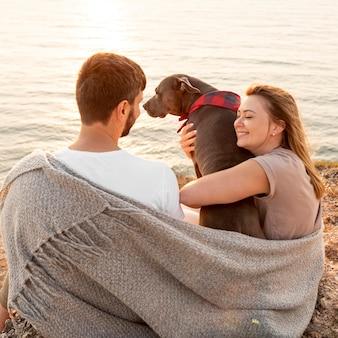 Paar, das den sonnenuntergang mit ihrem hund genießt