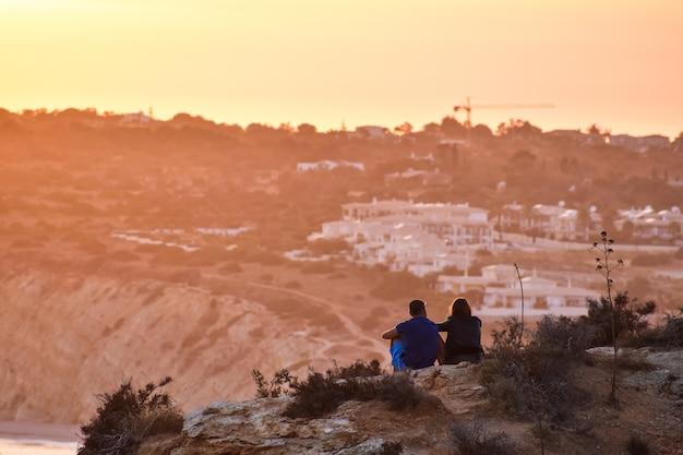 Paar, das den sonnenuntergang über dem strand bewundert