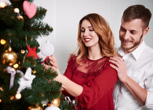 Paar, das den weihnachtsbaum verziert