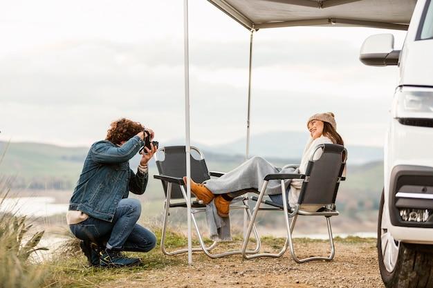 Paar, das die natur während eines roadtrips mit auto und kamera genießt