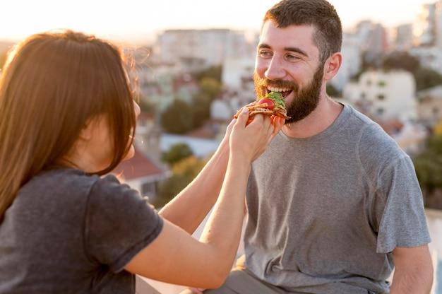 Paar, das draußen pizza isst