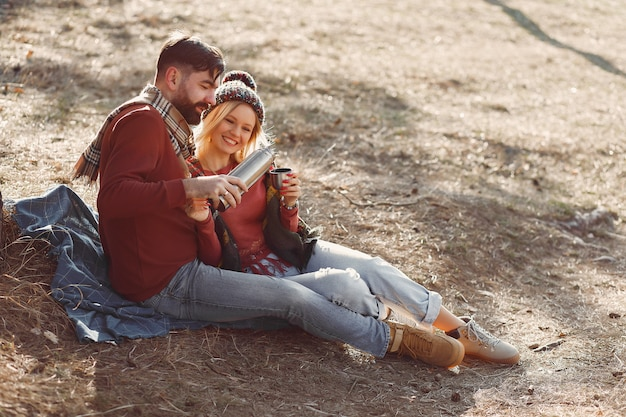 Paar, das durch einen baum in einem frühlingswald sitzt