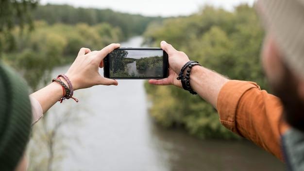 Paar, das ein foto der natur mit smartphone macht